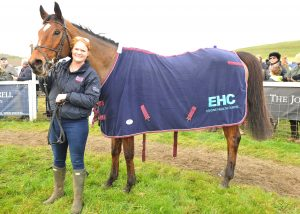 A woman holding a horse wearing an Equine Healh Centre cover