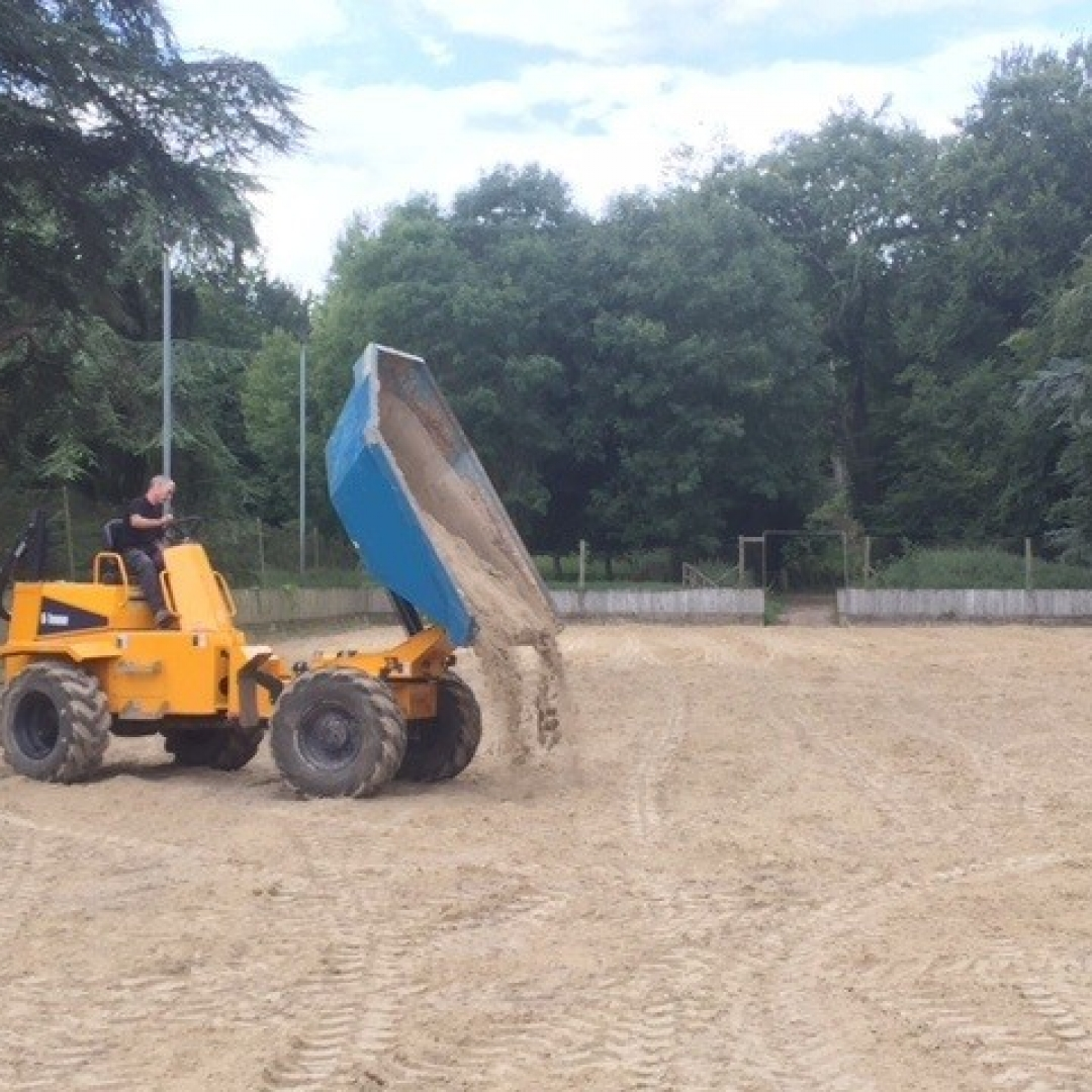 A dump truck adding fresh material to an equestrian surface