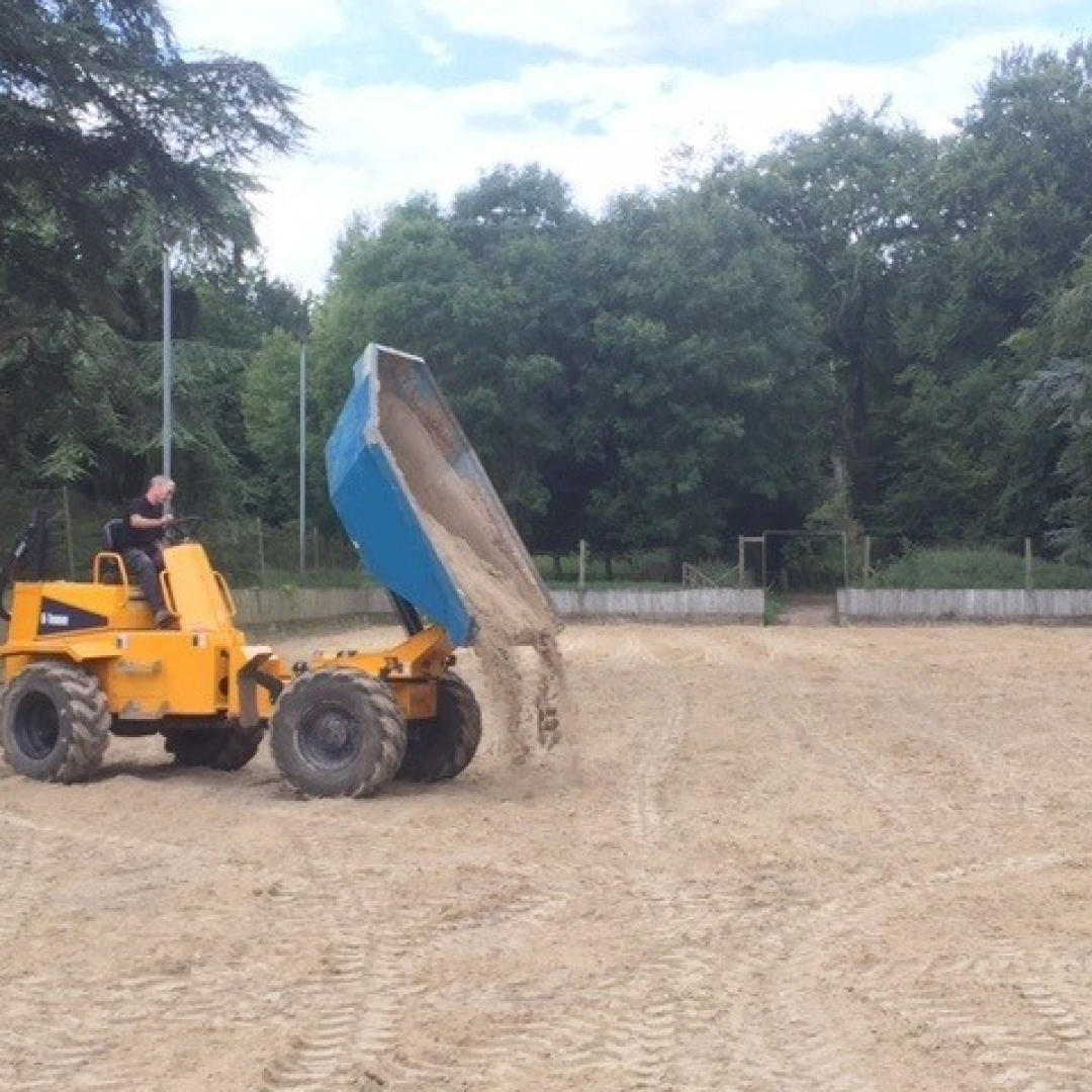 yellow dumper truck tipping sand into a horse riding arena