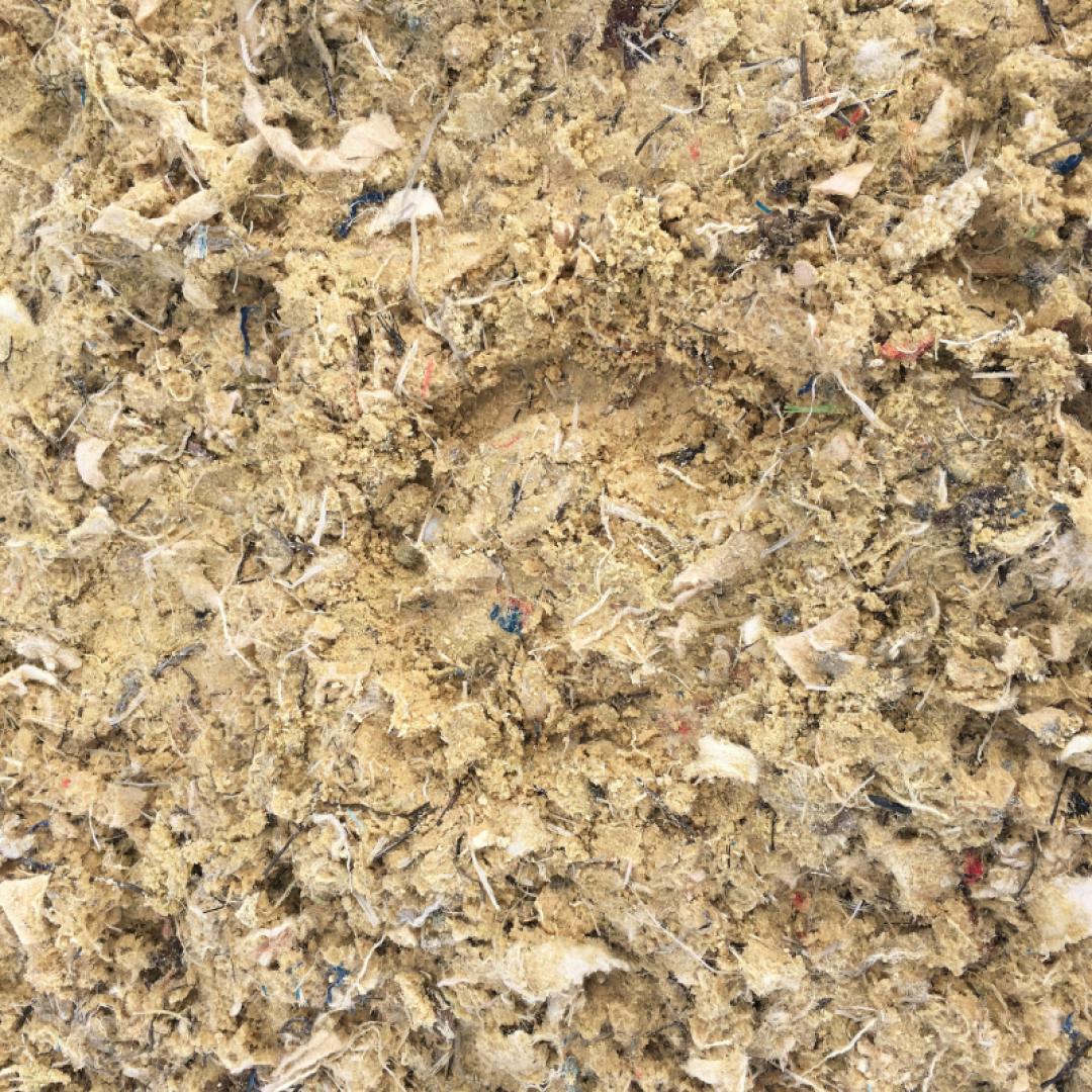 A horse hoof print in a sample of Equivia fibremix equestrian surface