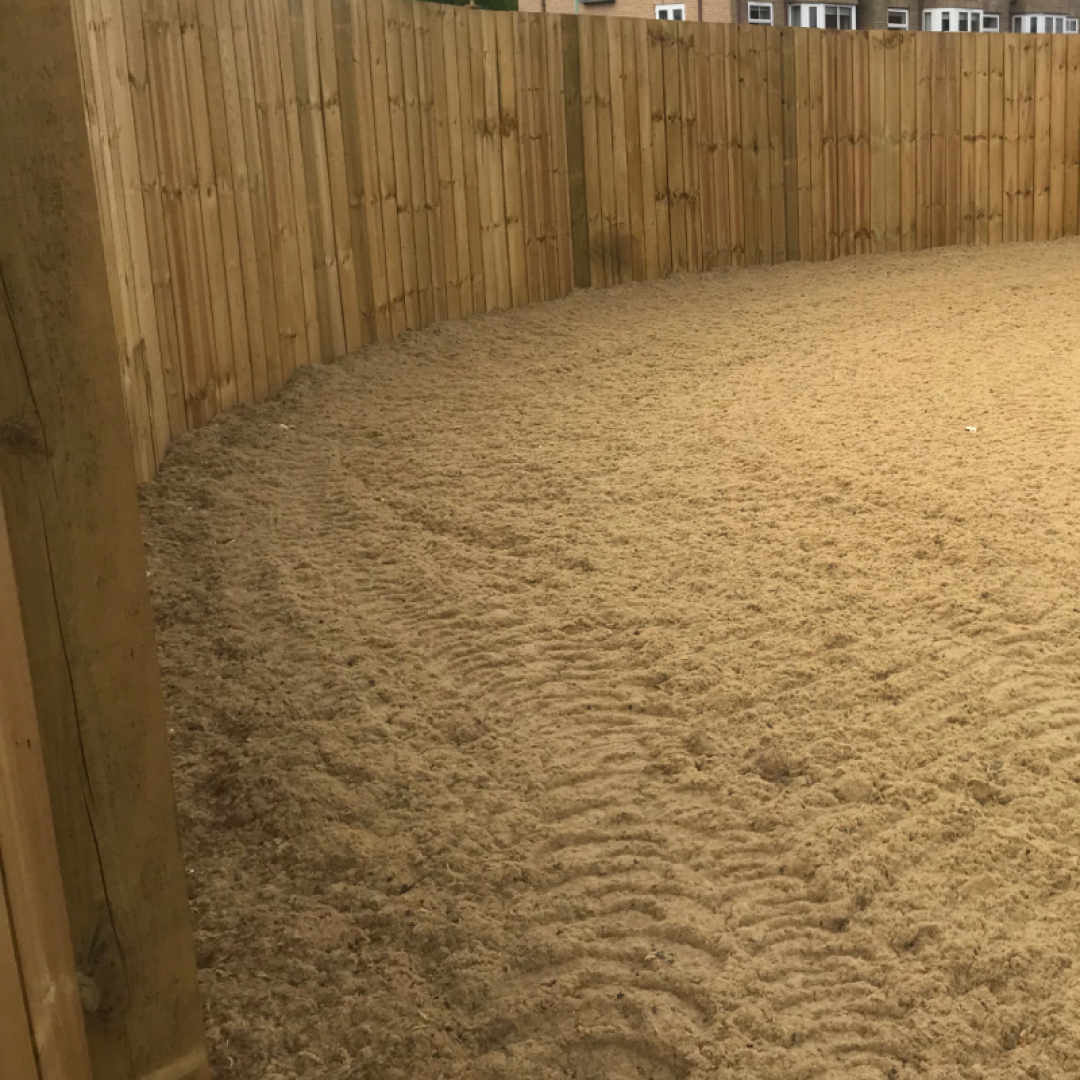 An outdoor riding arena with an Equivia equestrian surface