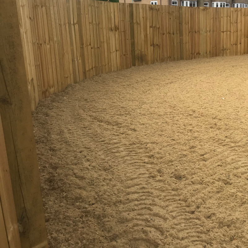 sand riding surface enclosed by closed board fencing